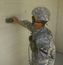 Soldier scanning building through wall.